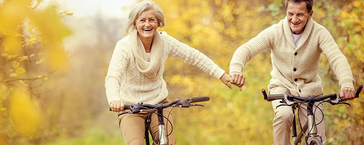 34112075 - active seniors riding bike in autumn nature. they relax outdoor.