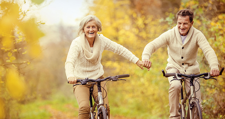 aging gracefully - active seniors riding bike in autumn